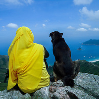 An Indonesian lady sitting next to a dog, on top of a mountain in Hong Kong, taken by Asti Maria.<br />