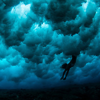 Silhouetted women enveloped in the clouds of a broken wave, underwater in Hawaii.