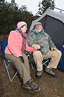 Senior couple relaxing by tent