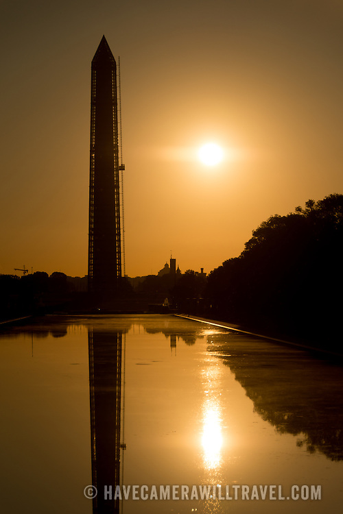 Sunrise at the Lincoln Memorial Reflecting Pool, with the Washington Monument silhouetted, in Washington DC.