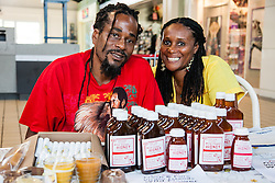 "Siblings Roniel Allembert (L) and Tiona Allembert are second generation beekeepers from St. Croix.  With over 350 hives, the pair present candles, lip balm, candles, soaps and more made with bee byproducts.  The VI Department of Agriculture hosts the second annual Fresh Beekeeping ""Buzzaar on St. Thomas.  The event which provided education and outreach featured an observation bee hive, and byproducts of hive production including soaps, balms, wines, candles, and beekeeping supplies.  Tutu Park Mall.  22 September 2012.  © Aisha-Zakiya Boyd"