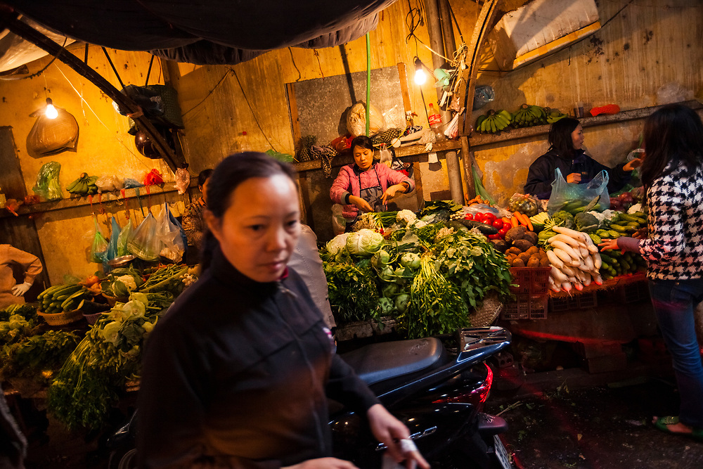 Shoppers and vendors at a local vegetable market in Hanoi, Vietnam.