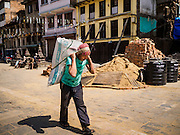 05 MARCH 2017 - KATHMANDU, NEPAL: A man carries a load past construction supplies for reconstruction from the 2015 earthquake. Much of Kathmandu is now a construction site because of rebuilding  two years after the earthquake of 25 April 2015 that devastated Nepal. In some villages in the Kathmandu valley workers are working by hand to remove ruble and dig out destroyed buildings. About 9,000 people were killed and another 22,000 injured by the earthquake. The epicenter of the earthquake was east of the Gorka district.     PHOTO BY JACK KURTZ