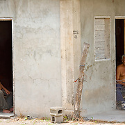 Two elderly brothers cooling off in the shade of their house, Yo Creek, Belize