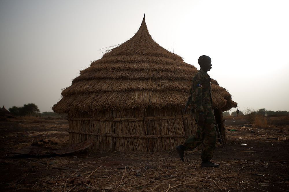 April 24, 2012 - Panakuach, South Sudan: A SPLA soldiers passes by a straw house at the last defensive line outside the village of Panakuach, 70 kilometers north of Bentiu...South Sudan and their northern neighbors, Sudan, have in the past two weeks been involved in heavily clashes over border disputes. Bentiu and neighboring villages have been under constant bombardment by the troops os Karthoum , who established their positions around 10 kilometers into South Sudan's territory. The international community is concerned about the possibility of a full on war between the two countries. (Paulo Nunes dos Santos/Polaris)