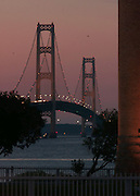 The Mackinaw Bridge, seen from Mackinaw City, glows in the sunset during prior to the fireworks displays to mark the bridges 50th anniversary.