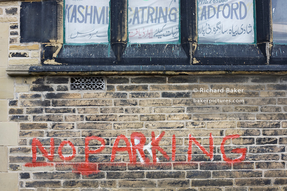 The words No Parking have been painted by hand on industrial bricks of a wall in a quiet street off Lumb Lane near Bradford city centre, Yorkshire. Above the message in the window is both Kashmiri and English writing for a mis-spelled business called Kashmir Catring Bradford.