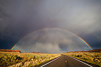A full rainbow and thunderstorm clouds over Scenic Highway 211 in Canyonlands National Park, Southeast Utah, USA.