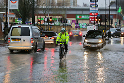 © Licensed to London News Pictures. 20/12/12/019. London, UK. A cyclist riding through the flood on Green Lanes, Harringay in North London, caused by overnight heavy rainfall and a pipe burst.  Photo credit: Dinendra Haria/LNP