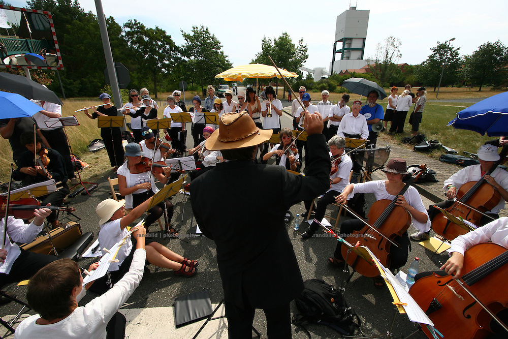 """60 musicians from the action group """"Lebenslaute"""", packed with instruments and music stands, climbed the four meter high wall around the site of the planned final nuclear waste storage site in Gorleben and began a protest concert with mainly classical music. Under the slogan """"A-Moll statt A-Müll"""" (A-minor instead of A(tomic)-waste"""" a varied and ambitious programme for choir and orchestra was being performed."""