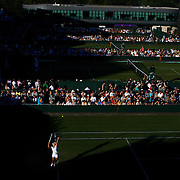 'Slam the Light'<br /> <br /> The summer light of the four tennis grand slams in Australia, France, England and USA provide an amazing contrast of light and condition, each tournament providing a uniqueness and beauty.<br />  From the harsh Australian summer light of Melbourne, to the spring light reflecting off the clay courts of Roland Garros in Paris, the low and late setting northern summer light casting beautiful long shadows on the lush Wimbledon grass in London and the early autumn soft subtle light of Flushing Meadows in New York.<br /> <br /> <br /> Akiko Morigami, Japan  in action  in the late evening light  during the first round match at the All England Lawn Tennis Championships at Wimbledon, London, England on Tuesday, June 23, 2009. Photo Tim Clayton.