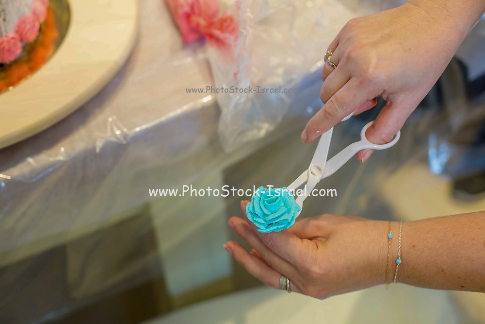 Decorating a birthday cake with blue icing sugar flowers