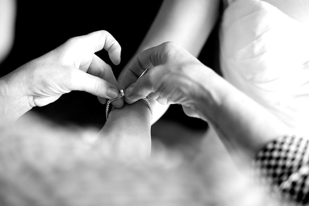 Die Mutter hilft der Baut das Armband, das sie zur Trauung anziehen wird, zu schließen.
