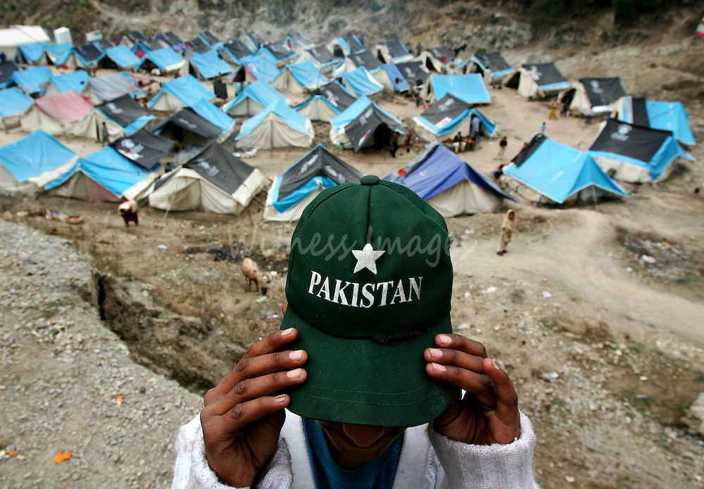 A Kashmiri boy adjusts his cap at the Mehnas tent camp on the outskirts of the earthquake-devastated city of Muzaffarabad in Pakistan-administrated Kashmir February 12, 2006. [Winter weather has made life more difficult for survivors of last year's massive earthquake in South Asia where more than two million people have been living in tents or crude shelters patched together from ruined homes.]