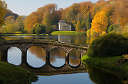 A autumn view of the bridge, lake and classical temple at Stourhead Landscape Garden, Stourton, Wiltshire, UK
