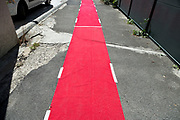 red carpet taped to the broken asphalt surface of the road