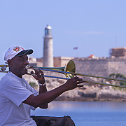 Trying to make a little money playing the trombone on El Malecon.<br /> Photography by Jose More