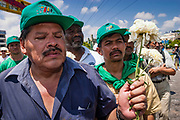 14 SEPTEMBER 2003 - CANCUN, QUINTANA ROO, MEXICO:  Mexican farmers carry a bouquet of flowers during a memorial service for Lee Kyung-hae, a South Korean farmer who committed suicided during a protest against liberalized agricultural trade at the WTO ministerial in Cancun. Tens of thousands of protesters, mostly farmers, came to Cancun for the fifth ministerial of the World Trade Organization (WTO). They were protesting against developed nations pushing to get access to agricultural markets in developing nations. The talks ultimately collapsed after no progress with no agreements reached between the participants.          PHOTO BY JACK KURTZ