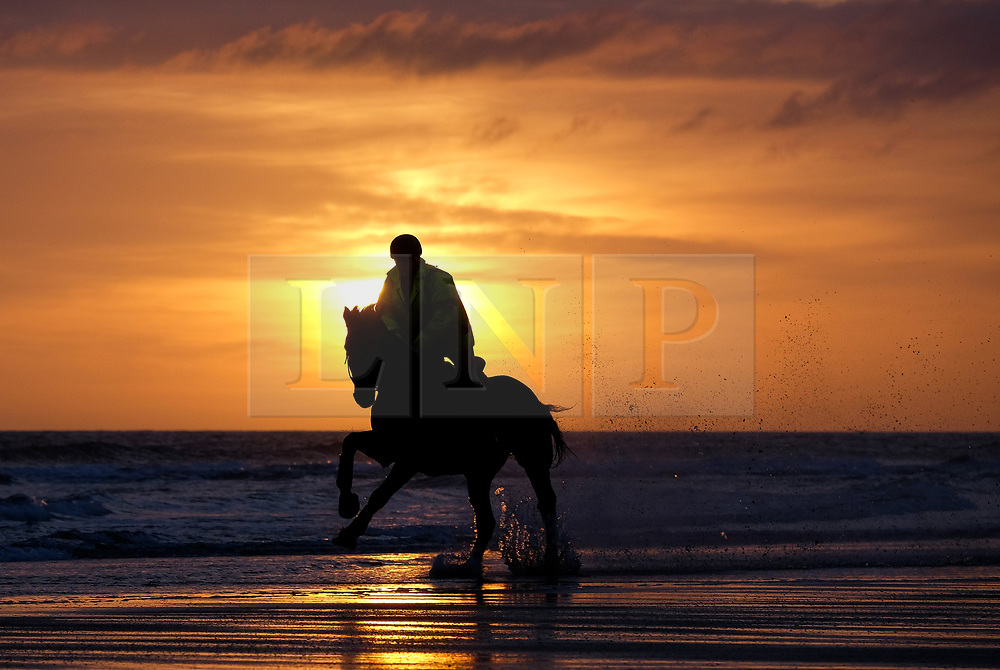 © Licensed to London News Pictures. <br /> 05/04/2017<br /> Saltburn-by-the-Sea, UK. <br />  <br /> A horse and rider gallop along the waters edge as the sun rises over the beach at Saltburn-by-the-Sea in North Yorkshire.<br /> <br /> Photo credit: Ian Forsyth/LNP