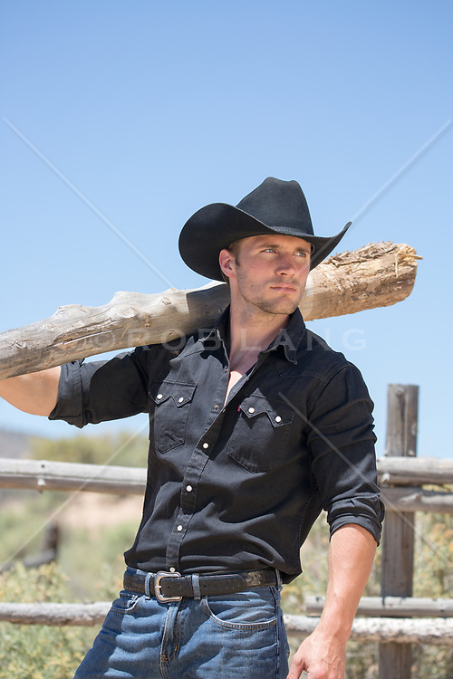 cowboy with a large piece of wood over his shoulder