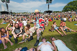 © Licensed to London News Pictures. 13/06/2014. Isle of Wight, UK.   A man in a Union Jack jacket sits amongst festival goers at the Main Stage at the Isle of Wight Festival the day before England is due to play its first game of the football World Cup. The Isle of Wight festival is an annual music festival that takes place on the Isle of Wight. Photo credit : Richard Isaac/LNP