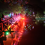 The lights of The Huc Bridge (Morning Sunlight Bridge) and the shoreline at night. The red-painted, wooden bridge joins the northern shore of the lake with Jade Island and the Temple of the Jade Mountain (Ngoc Son Temple).
