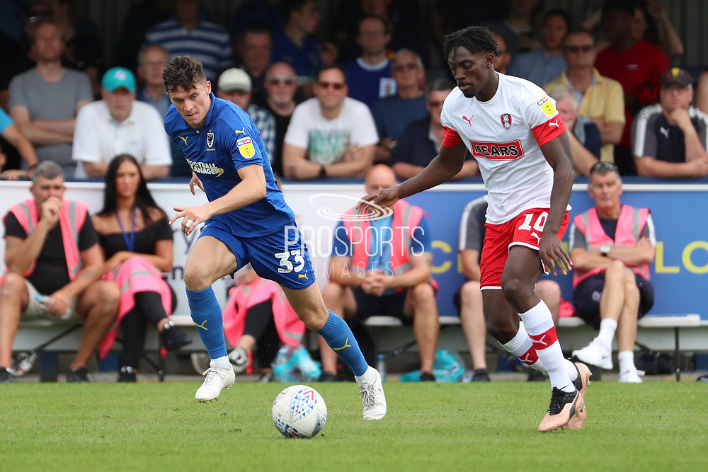 AFC Wimbledon midfielder Callum Reilly (33) chasing down Rotherham United attacker Freddie Ladapo (10) during the EFL Sky Bet League 1 match between AFC Wimbledon and Rotherham United at the Cherry Red Records Stadium, Kingston, England on 3 August 2019.