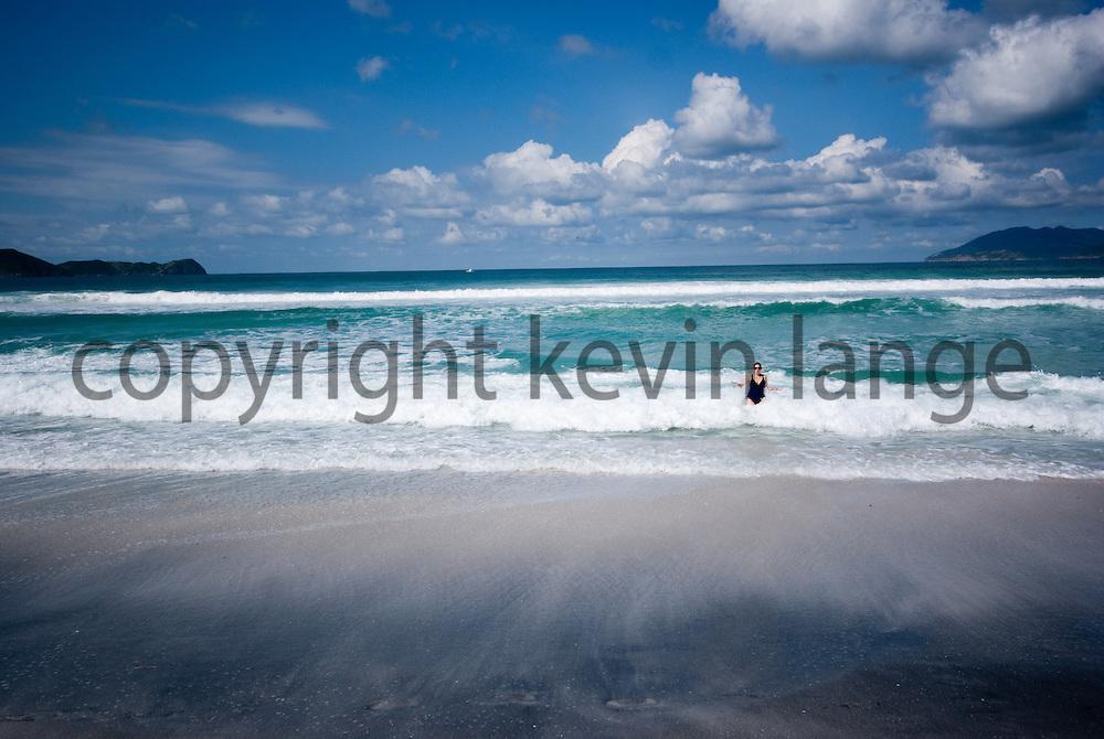 tourist ventures into the atlantic ocean waters at cabo frio beach in rio de janeiro, brazil