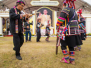 02 DECEMBER 2014 - BANGKOK, THAILAND: Akha hilltribe people perform a traditional dance on Sanam Luang in Bangkok before the Trooping of the Colors, during a celebration of the King's Birthday. The Thai Royal Guards parade, also known as Trooping of the Colors, occurs every December 2 in celebration of the birthday of Bhumibol Adulyadej, the King of Thailand. The Royal Guards of the Royal Thai Armed Forces perform a military parade and pledge loyalty to the monarch. Historically, the venue has been the Royal Plaza in front of the Dusit Palace and the Ananta Samakhom Throne Hall. This year it was held on Sanam Luang in front of the Grand Palace.    PHOTO BY JACK KURTZ