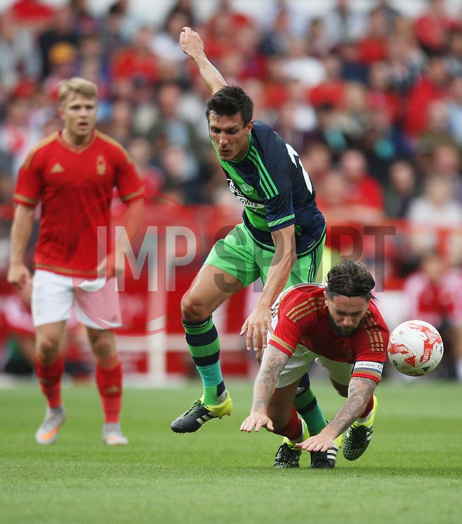 Henri Lansbury of Nottingham Forest (R) is fouled by Jack Cork of Swansea City<br /> <br />  - Mandatory by-line: Jack Phillips/JMP - 25/07/2015 - SPORT - FOOTBALL - Nottingham - The City Ground - Nottingham Forest v Swansea - Pre-Season Friendly