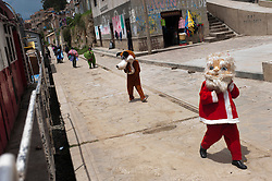 Christmas and other cartoon characters go on parade at one of the small stations on the tren macho's route.