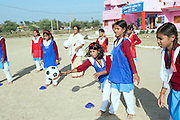 Ritu Gaur, 13, (centre) is throwing a ball towards her classmates while playing Circle Dodgeball in front of the Jamoniya Tank Girls Hostel, near Sehore, Madhya Pradesh, India, where the Unicef India Sport For Development Project has started in 2012. Covering 313 state-run girls' hostels and 207 mixed hostels in Madhya Pradesh, the project ensures that children from Scheduled Tribes (ST) and others amongst the poorest people in India, can easily access education and be introduced to sports. Field workers from Unicef also oversee their nutrition and monitor the overall conditions of each pupil.