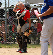 Licking Valley Lions catcher, Dillon Laymon,  pauses for a moment before putting his helot back on in the quarterfinal game against Med Ben.