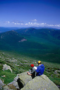 A man and woman enjoy the view from Mt. Lafayette, the highest point in the Franconia Range, overlooking the Pemigiwasett Wilderness Area, in the White Mountain National Forest, on a perfect summer day