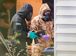 © Licensed to London News Pictures. 06/07/2018. Amesbury, UK. Police in protective suits and gas masks gather evidence at the house in Muggleton Road in Amesbury where a couple, named locally as Dawn Sturgess, 44, and her partner Charlie Rowley, 45, were taken ill on Saturday 30th June 2018. Police have confirmed that the couple have been in contact with Novichok nerve agent. Former Russian spy Sergei Skripal and his daughter Yulia were poisoned with Novichok nerve agent in nearby Salisbury in March 2018. Photo credit: Peter Macdiarmid/LNP