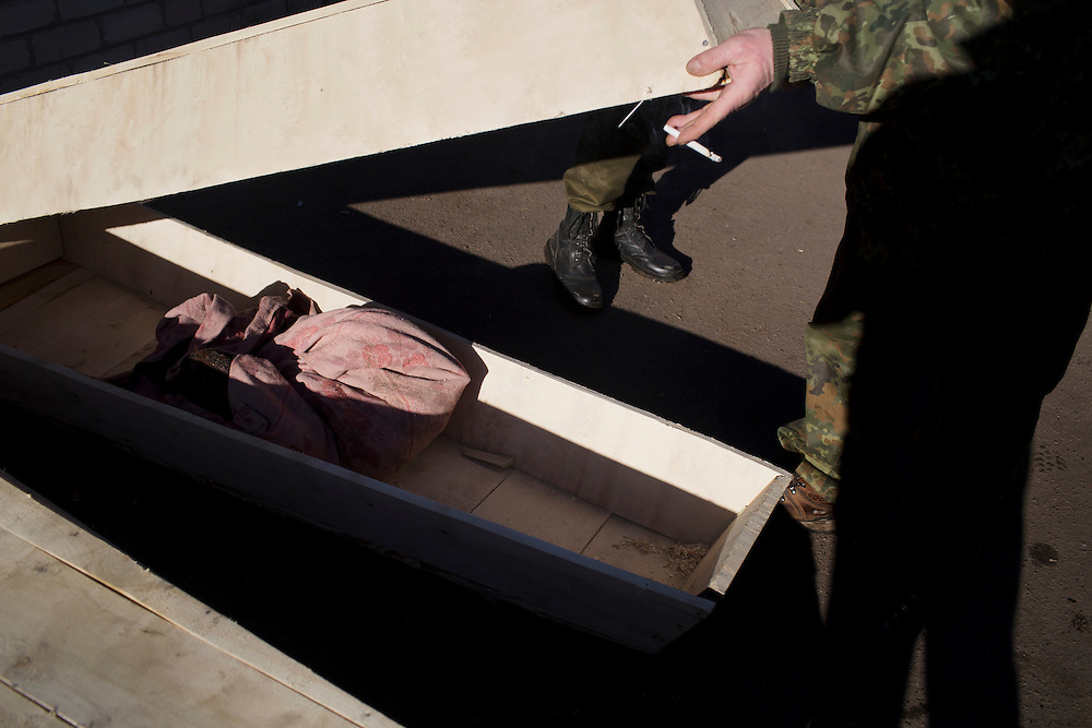 Soldiers at the morgue display a coffin containing what remains of one of their comrades on February 18, 2015 in Artemivsk, Ukraine.