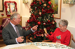 The Prince of Wales pulls a Christmas cracker with Barbara Stacey during a visit to the Sue Ryder Leckhampton Court Hospice near to Cheltenham in Gloucestershire, which he visits regularly and is celebrating 30 years of royal patronage.