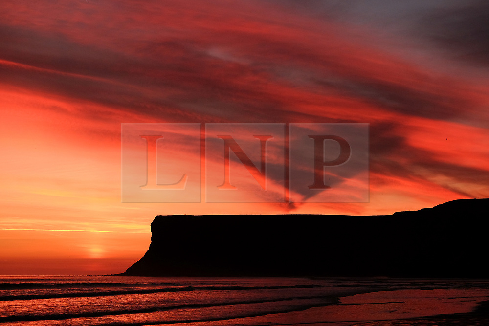© Licensed to London News Pictures. <br /> 26/03/20167. <br /> Saltburn by the Sea, UK.  <br /> <br /> A spectacular sunrise starts the day over Huntcliff in Saltburn by the Sea.<br /> <br /> Photo credit: Ian Forsyth/LNP