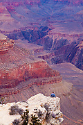 A visitor ponders the power of water, wind and time as he stares into the vastness of the Grand Canyon.