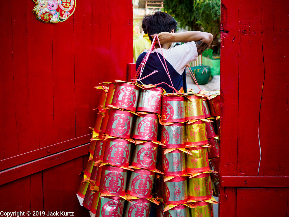 "26 FEBRUARY 2019 - BANGKOK, THAILAND: A man carries ""ghost gold"" into a Wat Mangon Kamalawat in Bangkok's Chinatown. Ghost gold is burned as an offering for ancestors. Bangkok has one of the largest ""Chinatown"" districts in the world. About 14% of all Thais have some Chinese ancestry and Chinese cultural practices are incorporated in many facets of Thai daily life.       PHOTO BY JACK KURTZ"