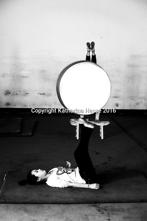 Wuqiao, April 20, 2016 : a young apprentee balances a drum during daily training. <br /> Acrobatic performances belong to Chinas variety arts and have existed for centuries. Acrobats originally were to entertain poor villagers in the countryside. Nowadays it's a profession for young people from the countryside seeking a better life in China's big cities where they lead a life as outcasts. Their monthly income is not enough to participate in social life , let alone to have private lifes. The troupes often live together in basic housing such as dorms and it's difficult to break out.