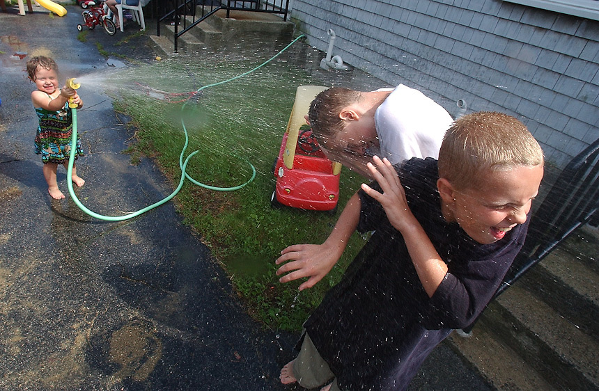 Gloucester: Thomas Grennan, 11, right, and his brother Michael, 13, get hosed down by their 2-year-old neighbour, Elizabeth Hawkins, 2, at Patriot's Circle Tuesday. The children were keeping cool by spraying each other with the hose.  (Photo by Mike Dean/Gloucester Daily Times). Tuesday, August 26, 2003 (NOTE: THIS IS A DIGITAL CAMERA IMAGE)..**************************************.Filter: Min (QMPro: Red Radius:0/Blue Radius:3/No Desp.).USM: Normal (Amt:200/Radius:0.3/Thresh:2).File Size: 7.49MB.Original file name: DSC_5578.JPG