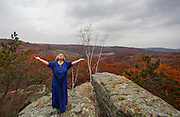 Rev. Selena Fox, senior minister and high priestess of Circle Sanctuary, a Wiccan church, offers a wellness blessing atop Spirit Rock at the sanctuary near Barneveld, Wis. (Photo @ Andy Manis)