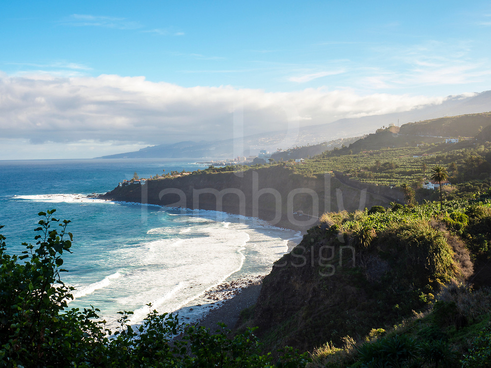Coast line landscape with cliffs and black sand beach and mountain Teide in background in the morning in winter, Tenerife, Spain