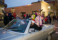 Amber and Mike Gagnon with their children Max and Olivia wave to the crowd with Max and Olivia as the Grand Marshalls of the annual Holiday Parade on Saturday evening.   (Karen Bobotas/for the Laconia Daily Sun)