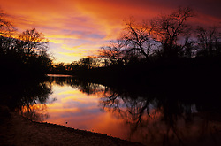 Stock photo of a sunset silhouette of trees along a Texas hill country river