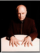 Brian Eno sitting with hands on table.