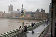 Tourists take photos on a dark and grey afternoon, across the Thames river from the Houses of Parliament on Westminster Bridge, on 19th October 2017, in London, England.