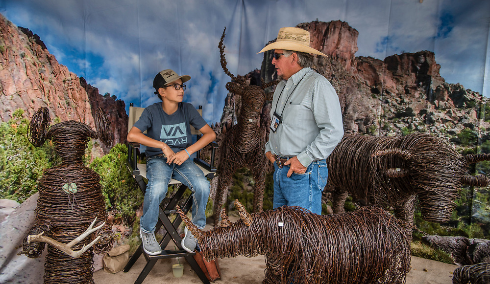 rer072917c/metro/July 29, 2017/Albuquerque Journal<br /> Ignacio (Buddy) Godinez(cq) speaks to his grandson Cade Griego(Cq),13, inside his stand during the annual Spanish Market in Santa Fe.  Godinez specializes in wired sculptures. <br /> Albuquerque, New Mexico Roberto E. Rosales/Albuquerque Journal