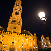Floodlights illuminate the famous Belfry (bell tower) in the Markt (Market Square) in the historic center of Bruges, a UNESCO World Heritage site.